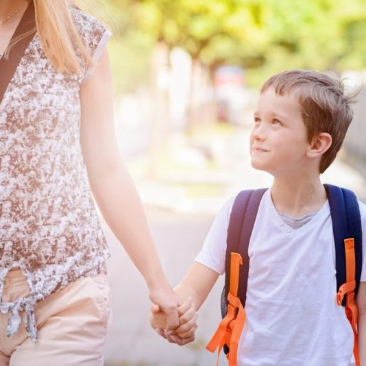 Au Pair walking a boy to school